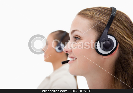 Side view of operators using headsets stock photo, Side view of operators using headsets against a white background by Wavebreak Media
