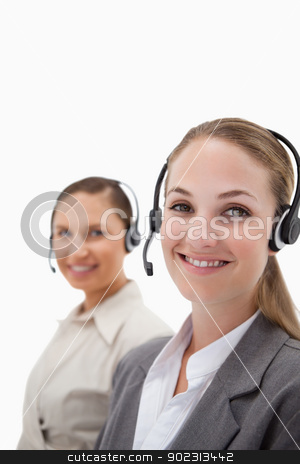 Portrait of young operators using headsets stock photo, Portrait of young operators using headsets against a white background by Wavebreak Media