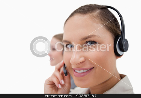 Young sales persons using headsets stock photo, Young sales persons using headsets against a white background by Wavebreak Media