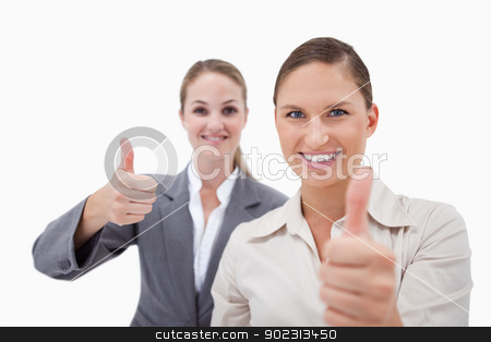 Smiling sales persons posing with the thumb up stock photo, Smiling sales persons posing with the thumb up against a white background by Wavebreak Media