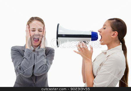 Manager yelling at her colleague through a megaphone stock photo, Manager yelling at her colleague through a megaphone against a white background by Wavebreak Media