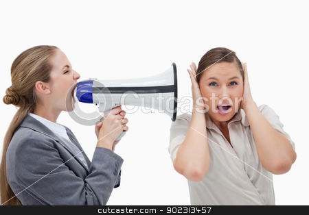 Businesswoman yelling at her coworker through a megaphone stock photo, Businesswoman yelling at her coworker through a megaphone against a white background by Wavebreak Media