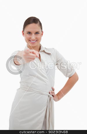Portrait of a smiling businesswoman pointing at the viewer stock photo, Portrait of a smiling businesswoman pointing at the viewer against a white background by Wavebreak Media