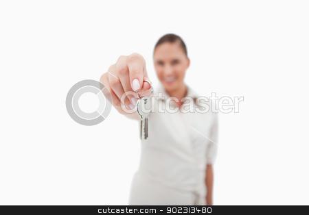Female real estate agent holding keys stock photo, Female real estate agent holding keys with the camera focus on the object by Wavebreak Media