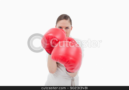 Businesswoman wearing boxing gloves stock photo, Businesswoman wearing boxing gloves against a white background by Wavebreak Media