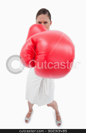 Portrait of an angry boxing businesswoman stock photo, Portrait of an angry boxing businesswoman against a white background by Wavebreak Media