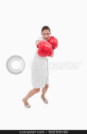 Portrait of a businesswoman punching someone stock photo, Portrait of a businesswoman punching someone against a white background by Wavebreak Media