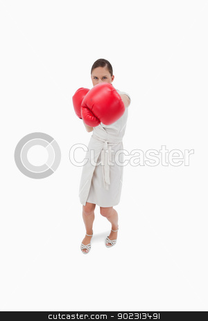 Portrait of a serious businesswoman punching someone stock photo, Portrait of a serious businesswoman punching someone against a white background by Wavebreak Media