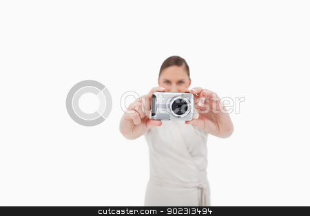 Young businesswoman taking a picture stock photo, Young businesswoman taking a picture against a white background by Wavebreak Media