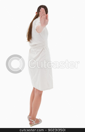 Portrait of a businesswoman turning her back while signing stop stock photo, Portrait of a businesswoman turning her back while signing stop against a white background by Wavebreak Media