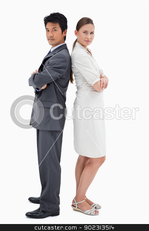 Portrait of business people standing back to back stock photo, Portrait of business people standing back to back against a white background by Wavebreak Media