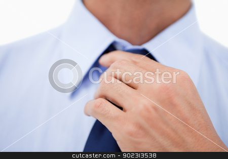 Close up of a hand fixing a tie stock photo, Close up of a hand fixing a tie against a white background by Wavebreak Media