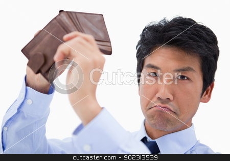 Businessman showing his empty wallet stock photo, Businessman showing his empty wallet against a white background by Wavebreak Media