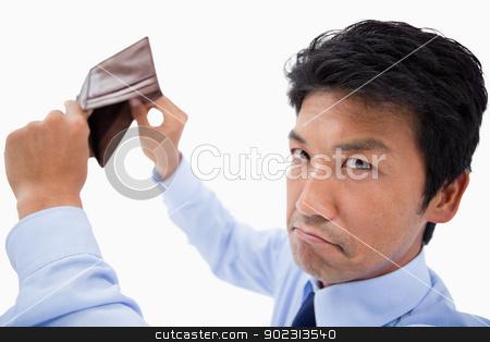 Broke businessman showing his empty wallet stock photo, Broke businessman showing his empty wallet against a white background by Wavebreak Media
