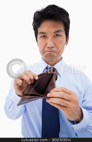Portrait of a businessman showing his empty wallet stock photo, Portrait of a businessman showing his empty wallet against a white background by Wavebreak Media