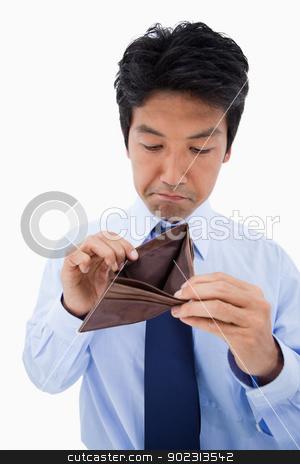 Portrait of a sad businessman showing his empty wallet stock photo, Portrait of a sad businessman showing his empty wallet against a white background by Wavebreak Media