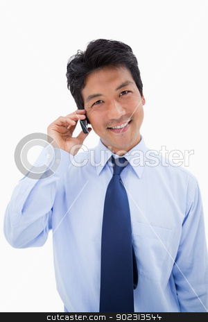 Portrait of a smiling businessman making a phone call stock photo, Portrait of a smiling businessman making a phone call against a white background by Wavebreak Media