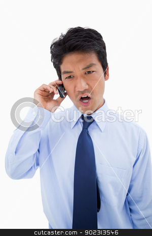 Portrait of an angry businessman making a phone call stock photo, Portrait of an angry businessman making a phone call against a white background by Wavebreak Media