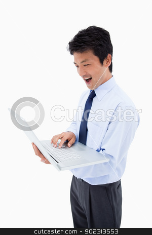 Portrait of a surprised businessman using a laptop stock photo, Portrait of a surprised businessman using a laptop against a white background by Wavebreak Media