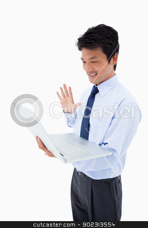 Portrait of a businessman waving at a laptop stock photo, Portrait of a businessman waving at a laptop against a white background by Wavebreak Media
