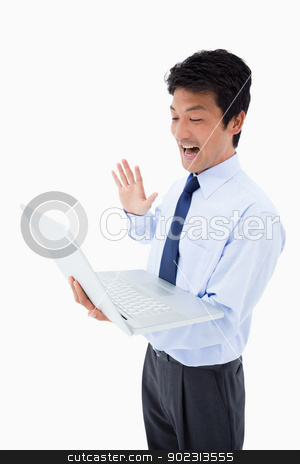 Portrait of a businessman waving at a notebook stock photo, Portrait of a businessman waving at a notebook against a white background by Wavebreak Media