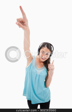 Portrait of a woman dancing while listening to music stock photo, Portrait of a woman dancing while listening to music against a white background by Wavebreak Media