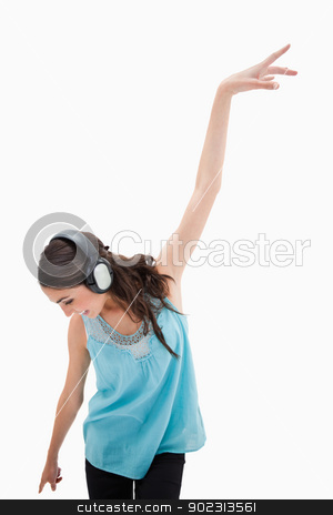 Portrait of a delighted woman dancing while listening to music stock photo, Portrait of a delighted woman dancing while listening to music against a white background by Wavebreak Media