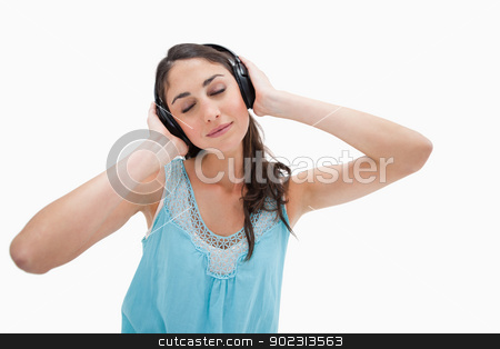 Woman listening to music stock photo, Woman listening to music against a white background by Wavebreak Media