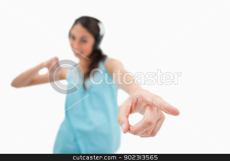 Cheerful woman dancing while listening to music stock photo, Cheerful woman dancing while listening to music against a white background by Wavebreak Media
