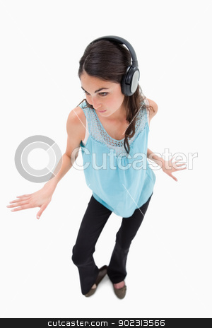 Portrait of a happy woman dancing while listening to music stock photo, Portrait of a happy woman dancing while listening to music against a white background by Wavebreak Media