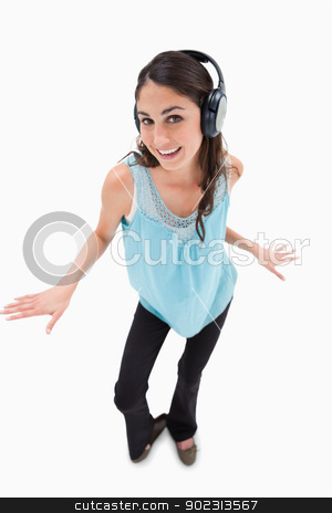 Portrait of a cheerful woman dancing while listening to music stock photo, Portrait of a cheerful woman dancing while listening to music against a white background by Wavebreak Media