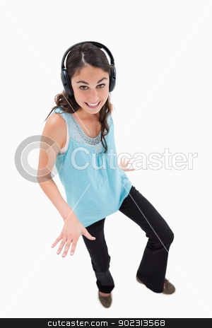 Portrait of a joyful woman dancing while listening to music stock photo, Portrait of a joyful woman dancing while listening to music against a white background by Wavebreak Media
