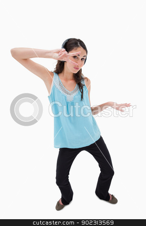 Portrait of a playful woman dancing while listening to music stock photo, Portrait of a playful woman dancing while listening to music against a white background by Wavebreak Media