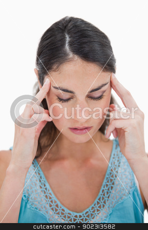 Portrait of a young woman having a headache stock photo, Portrait of a young woman having a headache against a white background by Wavebreak Media