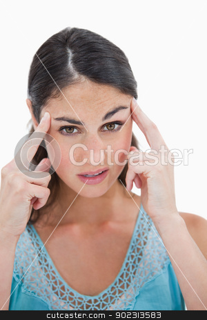 Portrait of a beautiful woman having a headache stock photo, Portrait of a beautiful woman having a headache against a white background by Wavebreak Media