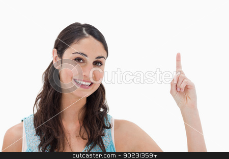 Woman pointing at a copy space stock photo, Woman pointing at a copy space against a white background by Wavebreak Media