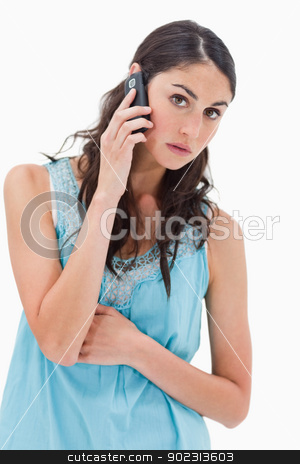 Portrait of a tired woman making a phone call stock photo, Portrait of a tired woman making a phone call against a white background by Wavebreak Media