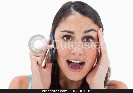 Shocked woman making a phone call stock photo, Shocked woman making a phone call against a white background by Wavebreak Media