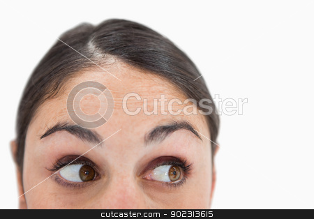 Close up of a woman looking away from the camera stock photo, Close up of a woman looking away from the camera against a white background by Wavebreak Media