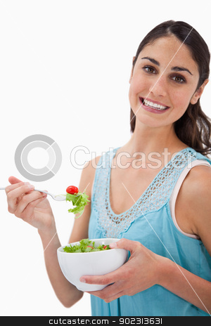 Portrait of a young woman eating a salad stock photo, Portrait of a young woman eating a salad against a white background by Wavebreak Media