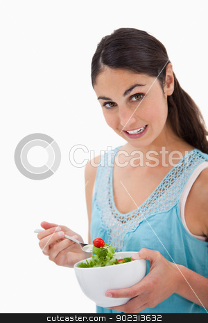 Portrait of a brunette woman eating a salad stock photo, Portrait of a brunette woman eating a salad against a white background by Wavebreak Media