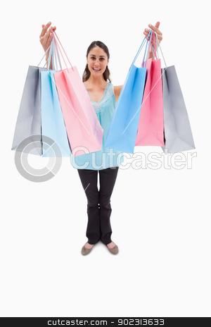 Portrait of a woman showing shopping bags stock photo, Portrait of a woman showing shopping bags against a white background by Wavebreak Media