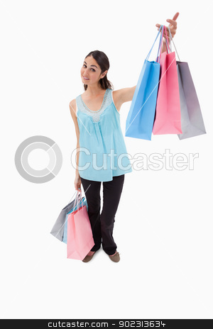 Portrait of a happy woman showing shopping bags stock photo, Portrait of a happy woman showing shopping bags against a white backgorund by Wavebreak Media