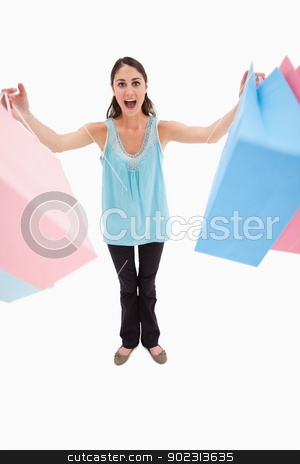 Portrait of a woman holding shopping bags stock photo, Portrait of a woman holding shopping bags against a white background by Wavebreak Media
