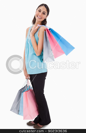Portrait of a woman posing with shopping bags stock photo, Portrait of a woman posing with shopping bags against a white background by Wavebreak Media