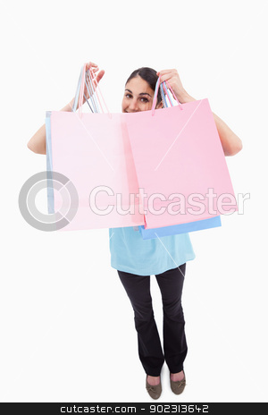 Portrait of a joyful woman showing shopping bags stock photo, Portrait of a joyful woman showing shopping bags against a white background by Wavebreak Media