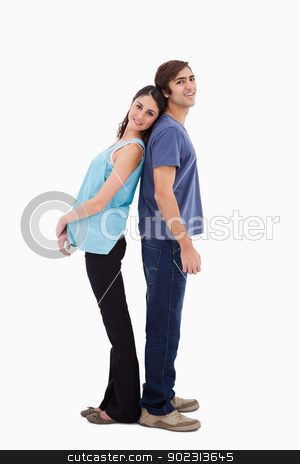 Portrait of a young couple standing back to back stock photo, Portrait of a young couple standing back to back against a white background by Wavebreak Media