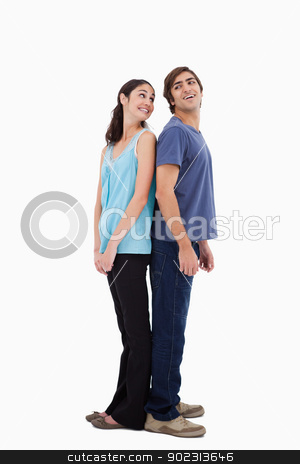 Portrait of a smiling couple standing back to back stock photo, Portrait of a smiling couple standing back to back against a white background by Wavebreak Media