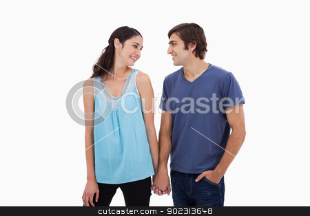 Young couple holding hands stock photo, Young couple holding hands against a white background by Wavebreak Media