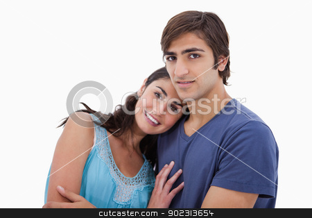 Charming couple embracing each other stock photo, Charming couple embracing each other against a white background by Wavebreak Media